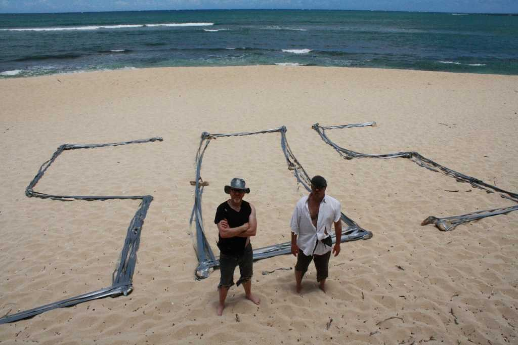 Episode Duct Tape Castaway/Island. Host Adam Savage and Jamie Hyneman on beach with duct tape 'SOS.'